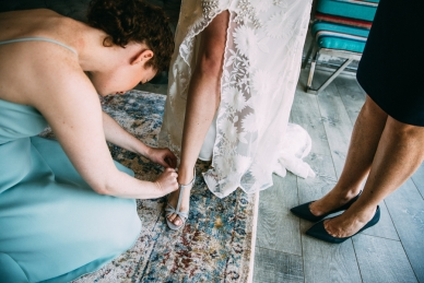 Bridesmaid helping bride photographed by Bright Bird Wedding Photography