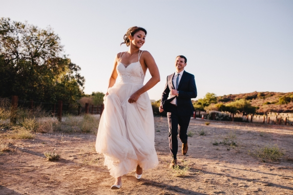 bride-and-groom-running-in-field