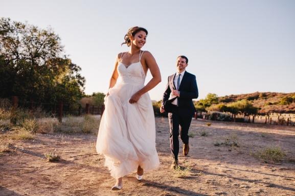 bride-and-groom-running-in-field
