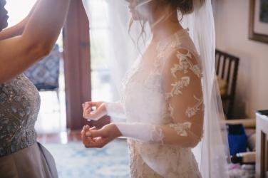 bridesmaid-placing-veil-on-bride