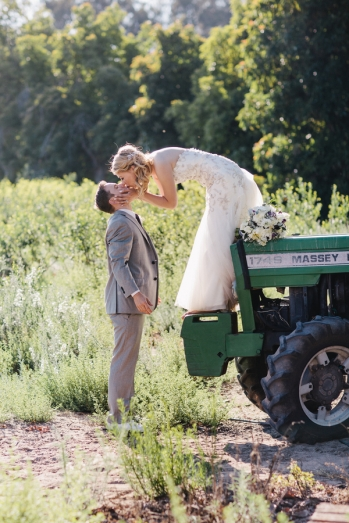 bride-on-tractor-kissing-groom
