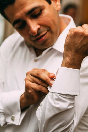 man-putting-on-cufflinks