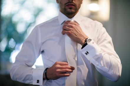 man-buttoning-white-dress-shirt