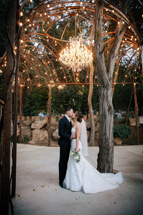 bride-and-groom-kissing-under-chandelier