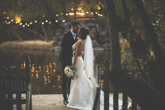 bride-and-groom-kissing-by-a-lake