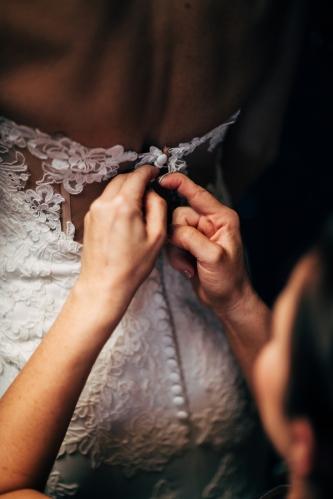 bridesmaid-helping-bride-with-wedding-dress