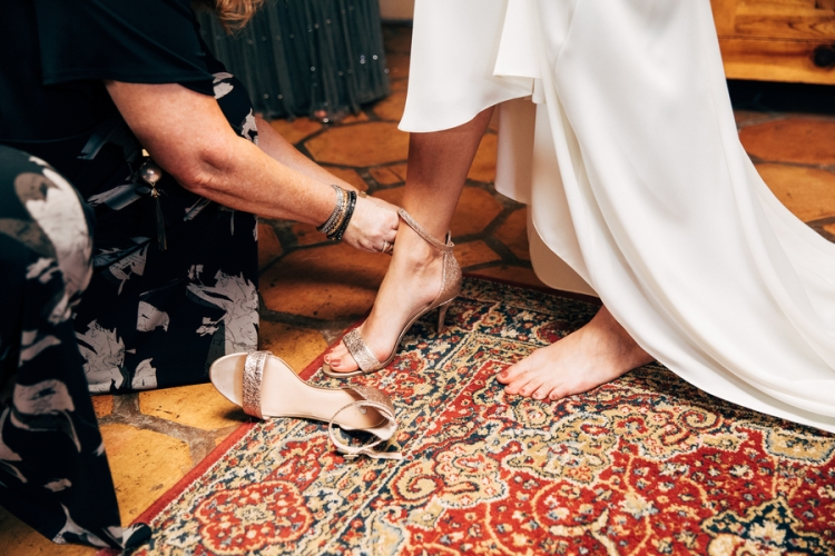 bridesmaid-helping-bride-with-shoes