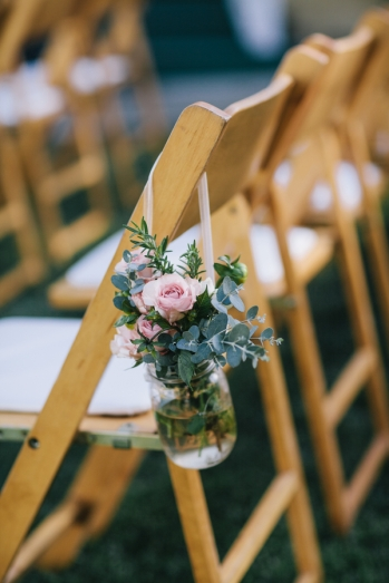 bouquet-in-jar-on-wedding-chairs