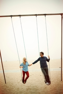 couple-holding-hands-on-swing-set