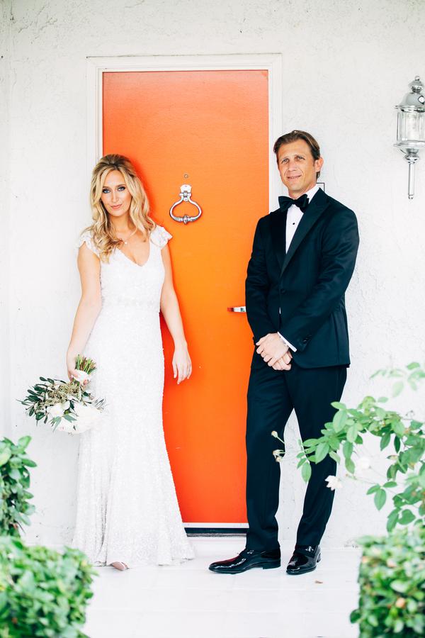 bride-and-groom-standing-by-orange-door